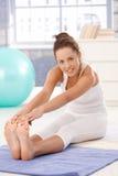 Aantrekkelijke vrouw die oefeningen op vloer doet Royalty-vrije Stock Afbeeldingen