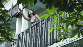Aantrekkelijke vrouw die op het balkon uitgaan en de hemel bekijken als het rainning stock video