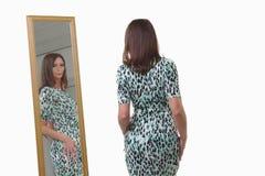 Aantrekkelijke vrouw die op middelbare leeftijd bezinning in spiegel bekijken royalty-vrije stock fotografie