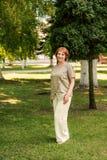 Aantrekkelijke vrouw die op middelbare leeftijd zich in een parkland op gras tussen bomen in linnen retro uitstekende kleren bevi royalty-vrije stock foto