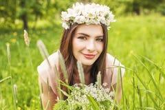Aantrekkelijke vrouw die op weide van groene gras en bloemen liggen royalty-vrije stock fotografie