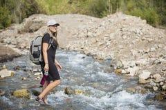 Aantrekkelijke Vrouw die over een bergstroom wandelen royalty-vrije stock afbeeldingen