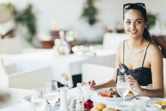 Aantrekkelijke vrouw die in restaurant eten stock afbeelding