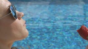 Aantrekkelijke vrouw die seductively zoete aardbei eten dichtbij pool, de zomerflirt stock footage