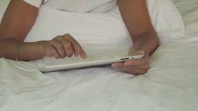 Aantrekkelijke vrouw die tablet in bed gebruiken stock footage
