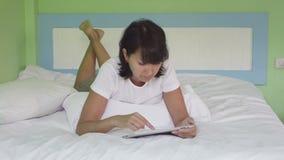 Aantrekkelijke vrouw die tablet in bed gebruiken stock video