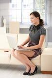 Aantrekkelijke vrouw die thuis gebruikend laptop werkt Stock Foto's