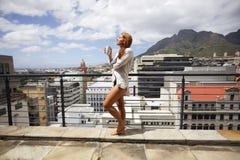 Aantrekkelijke vrouw die van zon op balkon met koffie genieten Stock Foto's