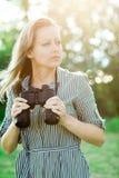Aantrekkelijke vrouw die verrekijkers openlucht in aard hebben stock foto