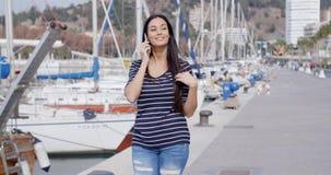 Aantrekkelijke vrouw die voorbij een jachthaven lopen stock videobeelden