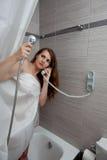 Aantrekkelijke vrouw die vraag in badkamers maakt Royalty-vrije Stock Afbeelding