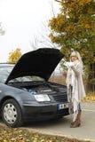 Aantrekkelijke vrouw die zich hulpeloos naast haar gebroken auto bevinden Royalty-vrije Stock Afbeeldingen