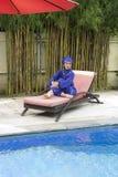 Aantrekkelijke vrouw in een Moslim swimwear burkini op een bed van de strandplank dichtbij de pool royalty-vrije stock afbeelding