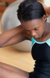 Aantrekkelijke vrouw in gymnastiekuitrusting die zitten-UPS doet Stock Afbeeldingen