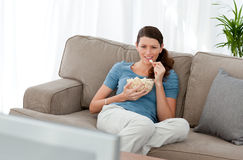 Aantrekkelijke vrouw het letten op televisie en het eten Stock Foto