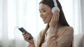 Aantrekkelijke vrouw het luisteren muziek in hoofdtelefoons, liefdesradiostation, plezier stock video