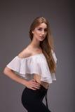 Aantrekkelijke vrouw in het witte blouse stellen over grijze achtergrond stock fotografie