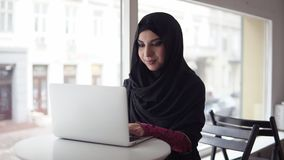 Aantrekkelijke vrouw in hijab die naar iets in Internet zoeken Portret van glimlachende jonge moslimvrouw die aan modern werken stock video