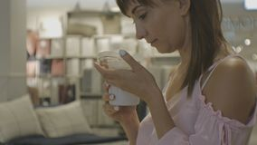 Aantrekkelijke vrouw in huishoudenwinkel Close-up van de jonge Kaukasische vrouwelijke kaars van het geurenaroma stock video
