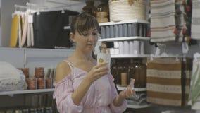 Aantrekkelijke vrouw in huishoudenwinkel Kaukasische vrouwelijke geuren bemerkte kaars stock footage
