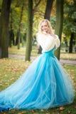 Aantrekkelijke vrouw in lange blauwe kleding in park blond Stock Foto's