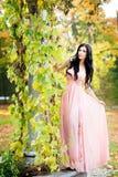 Aantrekkelijke vrouw in lange roze kleding in park Royalty-vrije Stock Afbeeldingen