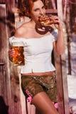 Aantrekkelijke vrouw in leerbroek met biermok en pretzel Stock Afbeeldingen