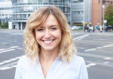 Aantrekkelijke vrouw met krullend blond haar buiten in de stad Royalty-vrije Stock Afbeelding