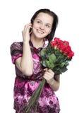Aantrekkelijke vrouw met rode rozen en telefoon stock foto