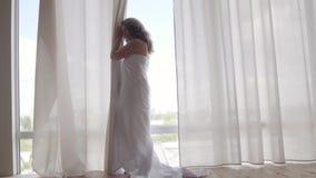 Aantrekkelijke vrouw omvat in zich dichtbij het vloer-aan-plafond venster bevinden en bedsheet die weg eruit zien Vrije tijd binn stock videobeelden