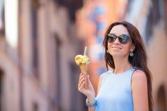 Aantrekkelijke vrouw op de straat die pret hebben en roomijs eten Jonge vrouwelijke model het eten roomijskegel op de zomerdag Royalty-vrije Stock Foto