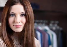 Aantrekkelijke vrouw tegen de achtergrond van kleren Stock Afbeeldingen