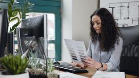 Aantrekkelijke vrouwelijke architect die aan de computer met kleur palatte in het moderne bureau werken stock videobeelden