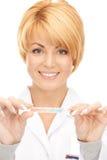 Aantrekkelijke vrouwelijke arts met thermometer Stock Afbeeldingen