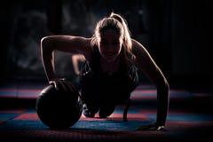 Aantrekkelijke vrouwelijke atleet die opdrukoefeningen op geneeskundebal uitvoeren Royalty-vrije Stock Foto's