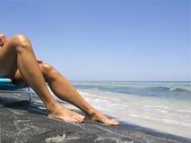 Aantrekkelijke vrouwelijke benen die op een mooi strand ontspannen Stock Afbeeldingen