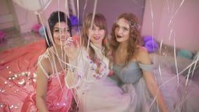 Aantrekkelijke vrouwelijke beste vrienden die mooie jonge vrouw op wang achter luchtballon kussen bij de verjaardagspartij van de stock videobeelden