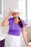 Aantrekkelijke vrouwelijke chef-kok die het recept bemonsteren Stock Fotografie