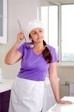 Aantrekkelijke vrouwelijke chef-kok die het recept bemonsteren Stock Foto