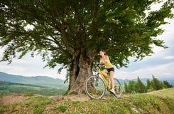 Aantrekkelijke vrouwelijke fietser met gele bergfiets, die van zonnige dag in de bergen genieten stock afbeeldingen