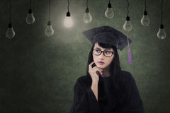 Aantrekkelijke vrouwelijke gediplomeerde onder lampen in klasse Royalty-vrije Stock Foto