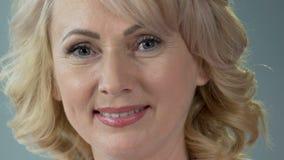 Aantrekkelijke vrouwelijke gepensioneerde die en camera, anti-leeftijdsmake-up glimlachen onderzoeken stock video