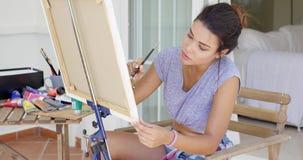 Aantrekkelijke vrouwelijke kunstenaar die aan een canvas werken stock videobeelden