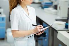 Aantrekkelijke vrouwelijke laboratoriumarbeider die medisch onderzoek naar modern laboratorium maken De documentenomslag van de w royalty-vrije stock foto
