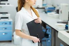 Aantrekkelijke vrouwelijke laboratoriumarbeider die medisch onderzoek naar modern laboratorium maken De documentenomslag van de w Royalty-vrije Stock Afbeelding