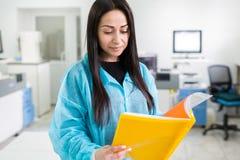 Aantrekkelijke vrouwelijke laboratoriumarbeider die medisch onderzoek naar modern laboratorium maken De documentenomslag van de w Stock Fotografie
