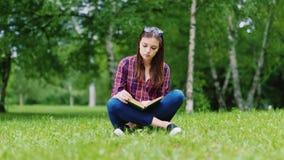 Aantrekkelijke vrouwelijke student die een boek in het park lezen, die op het gazon zitten stock footage