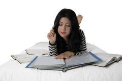 Aantrekkelijke vrouwelijke student die op bed bestuderen stock fotografie