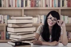 Aantrekkelijke vrouwelijke student en boeken bij bibliotheek Royalty-vrije Stock Afbeeldingen
