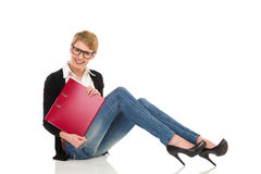 Aantrekkelijke vrouwelijke studentenzitting op de vloer met ringsbindmiddel. Stock Fotografie